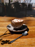 Uma xícara de café com marshmallows em um fundo de madeira da tabela Uma bebida do cacau em um copo da porcelana com uma colher d imagem de stock