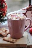 Uma xícara de café com o marshmallow na parte superior e nas cookies no livro imagem de stock