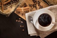 Uma xícara de café com preto de fumo roasted grãos de café e canela Em um fundo de madeira Vista superior e quadro para inscrição Fotografia de Stock