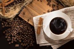 Uma xícara de café com preto de fumo roasted grãos de café e canela Em um fundo de madeira Vista superior e quadro para inscrição Fotografia de Stock Royalty Free