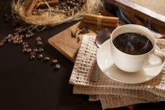 Uma xícara de café com preto de fumo roasted grãos de café e canela Em um fundo de madeira Vista superior e quadro para inscrição Foto de Stock