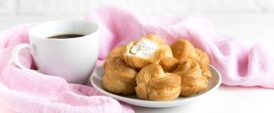 Uma xícara de café com profiteroles Fundo branco Café da manhã Composição macia com café Uma chávena de café em uma tabela foto de stock royalty free