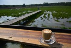 Uma xícara de café com projeto da arte na opinião da manhã foto de stock royalty free