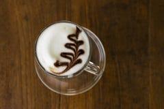 Uma xícara de café com teste padrão do coração em um copo branco na parte traseira de madeira Imagens de Stock Royalty Free