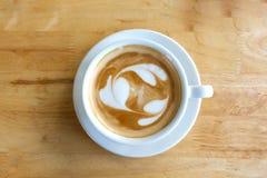 Uma xícara de café com teste padrão do coração em um copo branco no tabl de madeira Foto de Stock Royalty Free