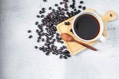 Uma xícara de café e feijões de café em um fundo branco fotografia de stock