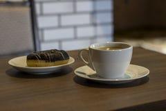 Uma xícara de café e uma filhós imagens de stock