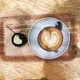uma xícara de café e uma sobremesa da forma do coração Foto de Stock Royalty Free