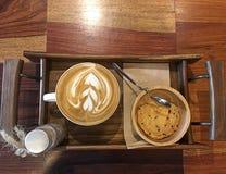 Uma xícara de café e um biscoito na bandeja de madeira Imagem de Stock