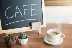 Uma xícara de café e um cacto com quadro do menu do quadro-negro na tabela de madeira no café Imagem de Stock