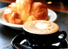 Uma xícara de café e um croissant Fotografia de Stock