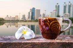 Uma xícara de café e um plumeria na tabela de madeira com fundo do céu azul Imagens de Stock