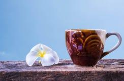 Uma xícara de café e um plumeria na tabela de madeira com fundo do céu azul Fotografia de Stock Royalty Free