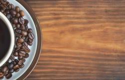 Uma xícara de café em uns pires com os feijões de café fritados, colocados à esquerda Foto de Stock