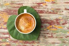 Uma xícara de café na folha verde imagens de stock royalty free