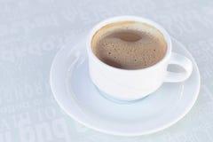 Uma xícara de café na placa na tabela Imagens de Stock