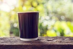 Uma xícara de café na tabela de madeira com fundo do bokeh Imagens de Stock Royalty Free