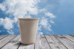 Uma xícara de café na tabela de madeira com fundo do céu azul Fotografia de Stock Royalty Free
