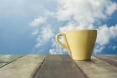 Uma xícara de café na tabela de madeira com fundo do céu azul Imagem de Stock Royalty Free