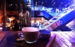 Uma xícara de café na tabela de madeira em uma cafetaria foto de stock royalty free