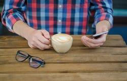 Uma xícara de café nas mãos do ` s dos homens fotos de stock