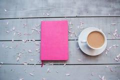 Uma xícara de café, um ramalhete das flores, um diário, um caderno, uma pena cor-de-rosa e um telefone em um fundo cinzento, fotos de stock royalty free