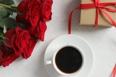 Uma xícara de café, um ramalhete de rosas vermelhas e um presente com uma fita vermelha no close-up da tabela fotografia de stock royalty free