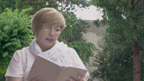 Uma zorra de um assento envelhecido bonito da mulher exterior e de ler um livro vídeos de arquivo