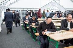 Uman, de Oekraïne, 13 09 2015: Heel wat Joodse mensen in Kippahs en zwarte kleren zijn binnen zitten bij de lijst en lezen boeken royalty-vrije stock afbeeldingen