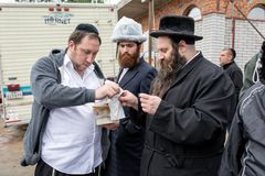 Uman,Ukraine, 13.09.2015: A Jewish men in Kippahs and black clothes get ready to eat outdoors royalty free stock photography