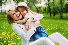 Umarmen der glücklichen Mutter und der Tochter für einen Weg im Park auf dem grünen Rasen Stockfotografie