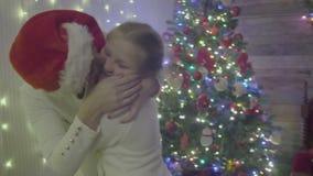 Umarmen der Mutter und der Tochter nahe dem Weihnachtsbaum stock footage