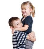 Umarmen des liebevollen Bruders und der kleinen Schwester lokalisiert über Weiß Stockbilder