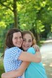 Umarmen mit zwei junges Jugendfreunden Lizenzfreie Stockfotos