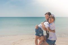 Umarmendes und glaubendes Glück der Frau und des Kindes auf Sandstrand mit Meerblickansicht in den Hintergrund stockfotografie