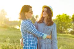 Umarmung des Elternteils und des Jugendlichen, der Mutter und der Tochter mit 14 Jährigen, die in der Natur lächeln lizenzfreie stockfotos