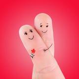 Umarmung des glücklichen Paars mit dem Blumenkonzept, gemalt an den Fingern Lizenzfreie Stockfotos