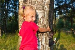 Umarmung des kleinen Mädchens ein Baum stockfotografie