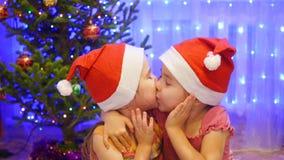 Umarmung und Kuss mit zwei Schwestern am Weihnachtsfest Im Hintergrund Lichtgirlanden der Tanne Stockfoto