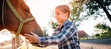 Umarmungspferd des kleinen Mädchens Stockbild