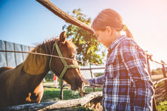 Umarmungspferd des kleinen Mädchens lizenzfreies stockfoto