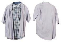 Umas camisas cinzentas quadriculado e contínuas velhas amarrotadas do ` s do homem penduram sobre Foto de Stock Royalty Free