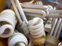 Umas lâmpadas fluorescentes mais velhas são recolhidas em um recipiente para a eliminação Fotos de Stock Royalty Free