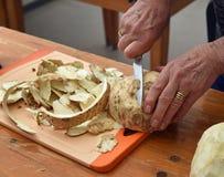 Umas mãos fêmeas mais velhas cortaram o aipo com uma faca de cozinha em um t de madeira Imagens de Stock Royalty Free