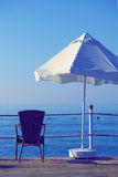 Umbrela和扶手椅子在海 库存照片