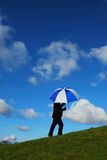 Umbrella. Person walks uphill holding umbrella Stock Photo