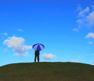 Umbrella. Person stands on a horizon holding umbrella Stock Image