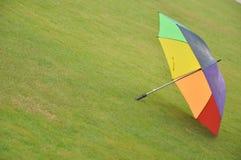 Umbrella. Multicolor umbrella placed over wet lawn Stock Photography