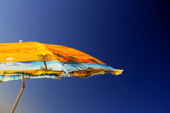 Umbrella. Yellow umbrella over a clear blue sky in a hot summer day on the beach Royalty Free Stock Photography