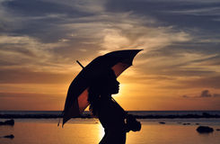 Umbrella. Lady's silhouette, holding an umbrella, at Sunset, at the beach Royalty Free Stock Photo